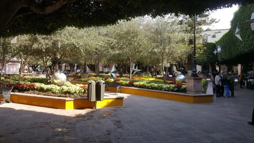 A large plaza with several trees and people standing around.