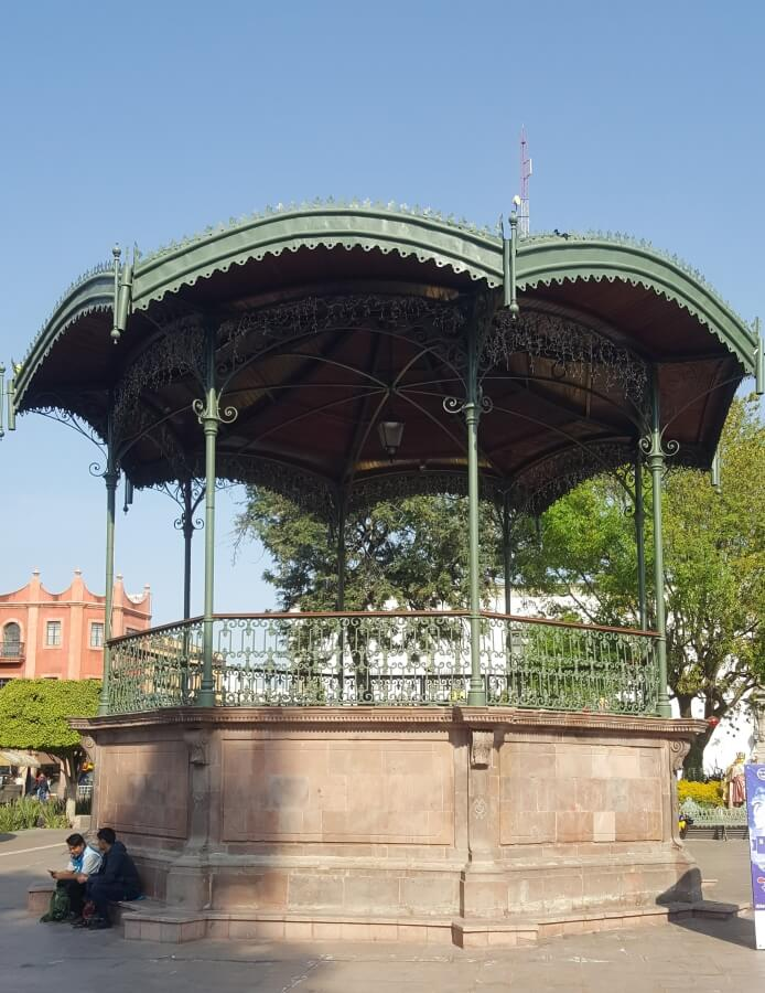 A stone gazebo with a green roof.