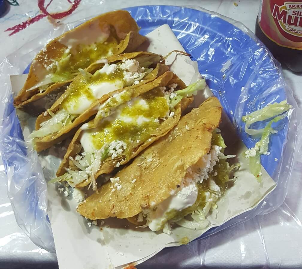Tacos with different fillings, lettuce, cheese, and cream.