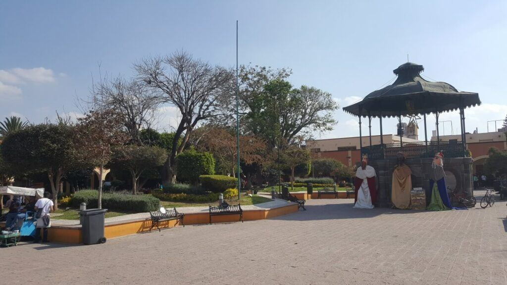 A large plaza with trees and a gazebo.