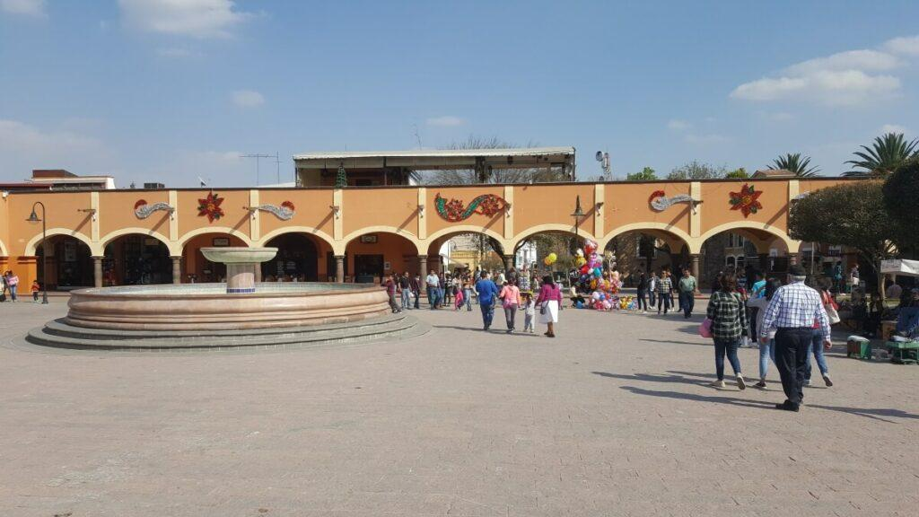 A giant plaza with yellow portals and a fountain.