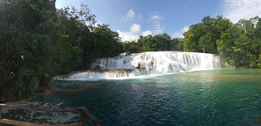 A waterfall with turquoise water below it.