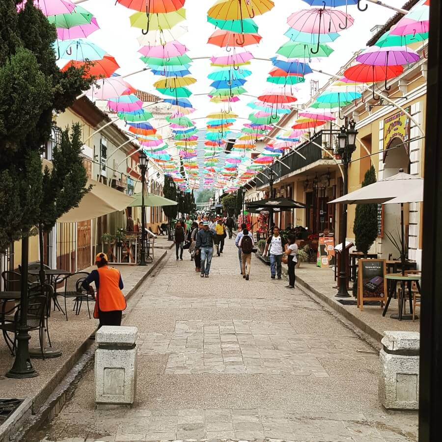 A street with lots of colorful umbrellas over it.