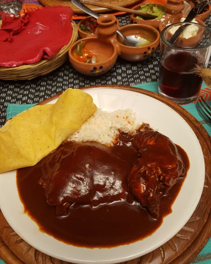 A plate with mole, rice, and a tortilla.