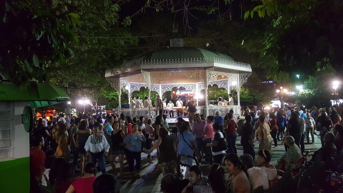 A crowd dancing around a green gazebo at night.