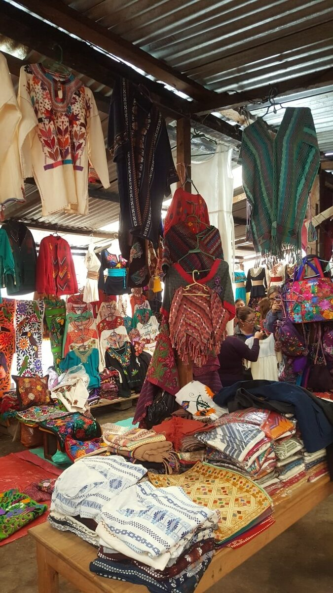 Lots of colorful clothes made by hand at a local market.
