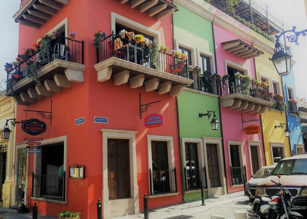 A colorful building painted in red, green, pink, yellow, and blue with balconies with flowrpots.