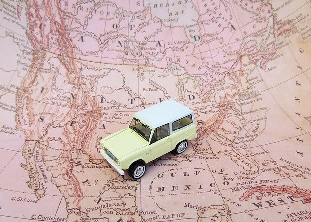 A tan car traveling over a pink map.