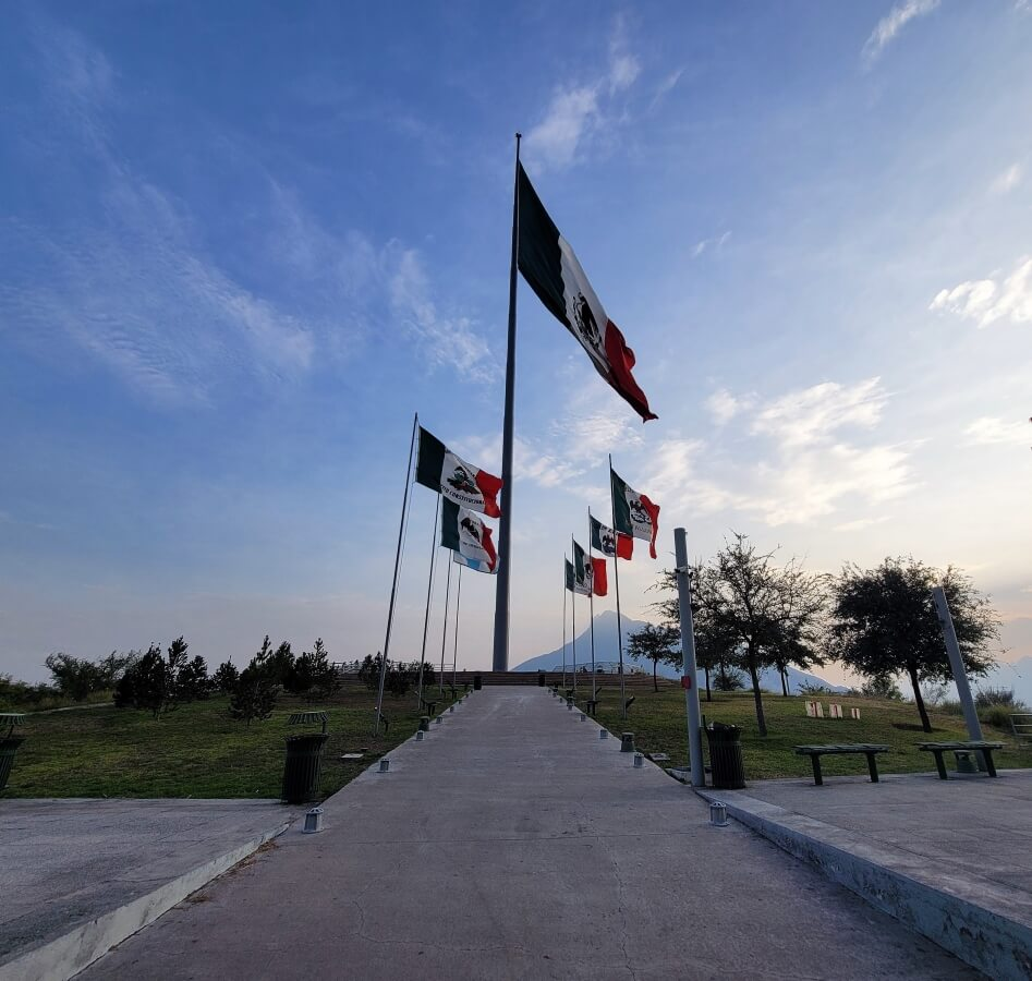 An observation deck with several Mexican flags waving in the air.