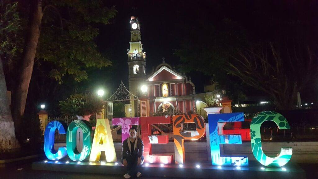 A red and yellow church lit up at night with the letters Coatepec in front of it.