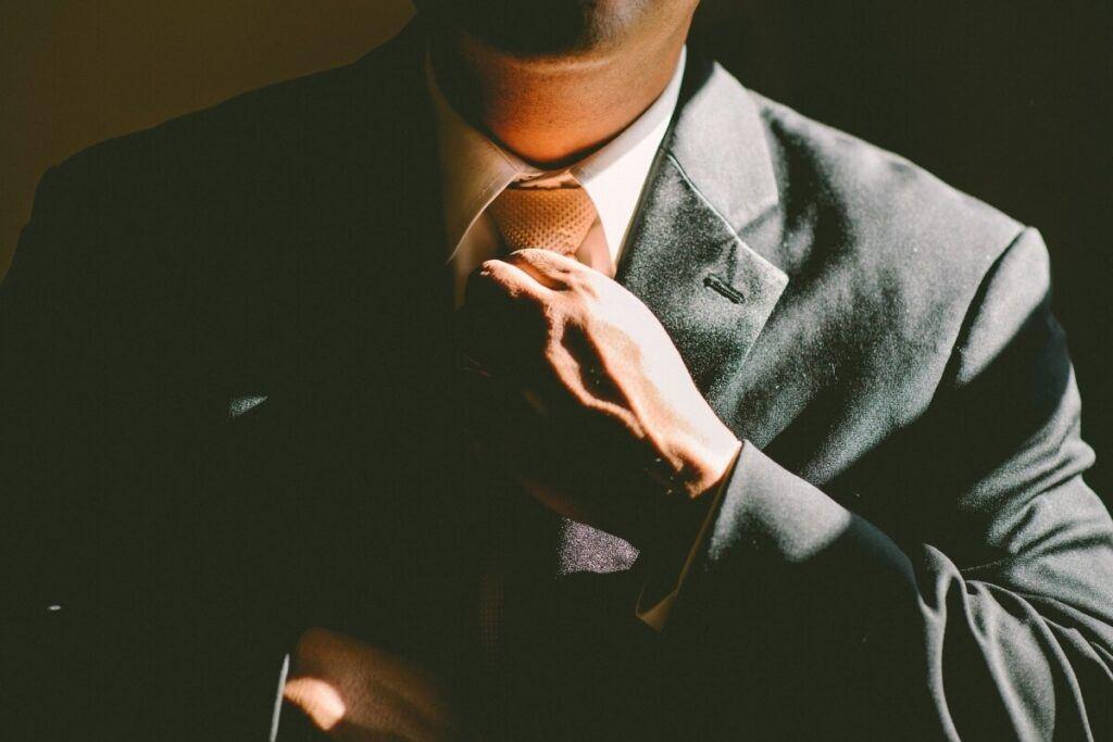 A man adjusting his tie.