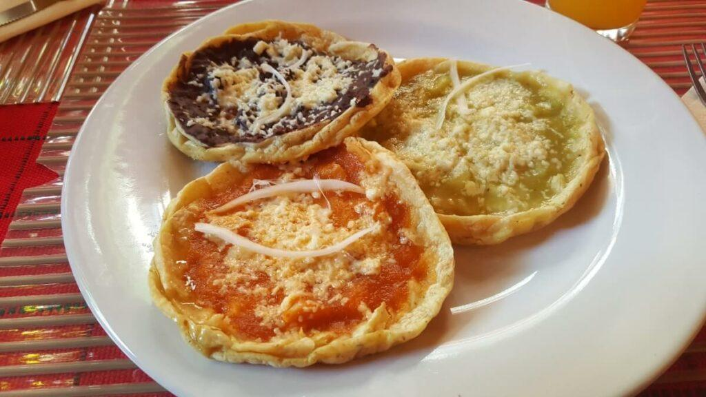 Three picaditas with sauce and cheese.