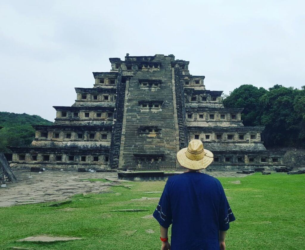 A young man dressed in blue looking at a pyramid.