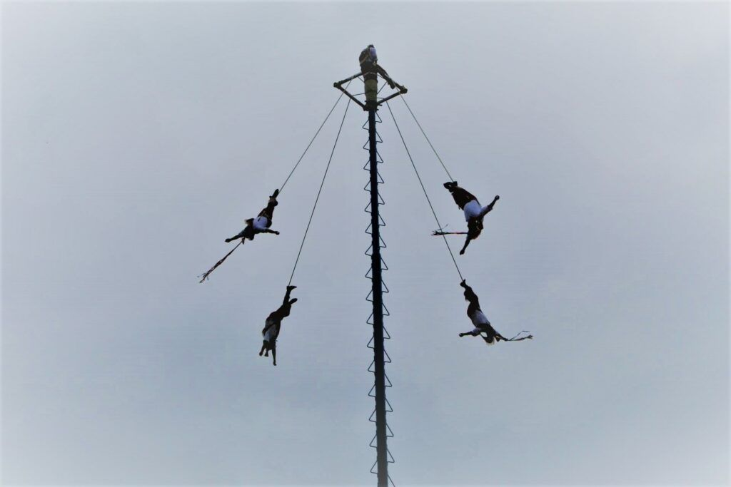 Four men tied by their feet and suspended in the air.