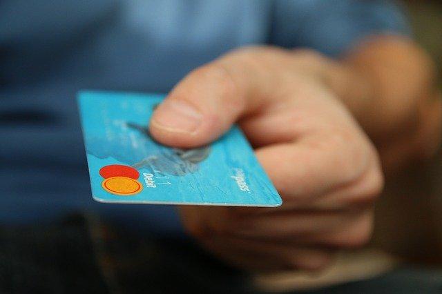 A hand holding a blue debit card.